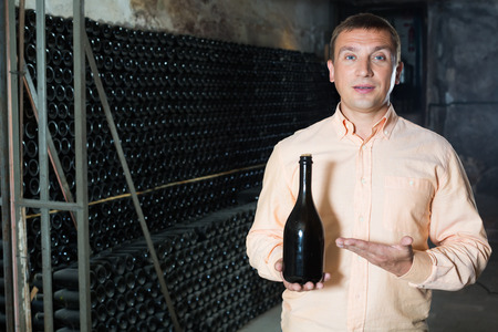 male customer holding bottle of red wine from dusty shelves