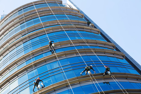 Group of industrial alpinists washing windows of skyscraper Reklamní fotografie