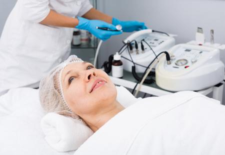 mujer de mediana procedimientos de toma de belleza para la cara en salón del balneario