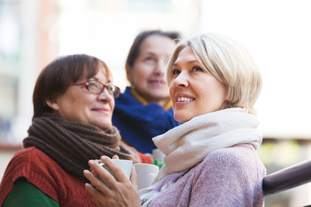 Group of smiling senior female friends drinking tea at balcony. Focus on blonde