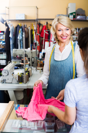 smiling mature woman employee bringing clothing from customer in sewing studio