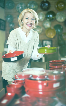 Mature female holding ceramic cookware at workshop and smiling