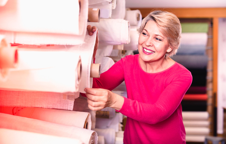 Happy cheerful positive mature female shopper searching for suitable fabric in textile shop