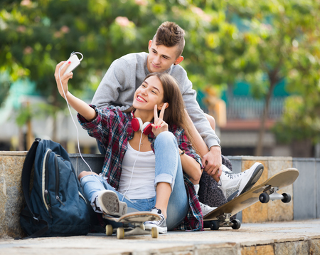 16s: Two happy teenagers smiling and doing selfie together on the smartphone outdoors