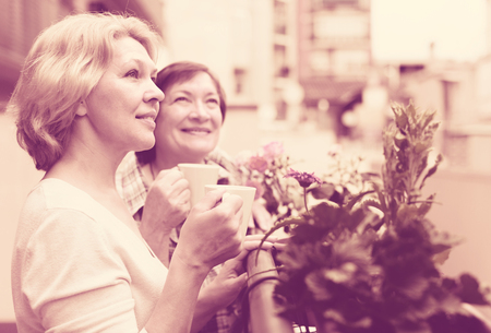 Two happy mature pensioners drinking tea on balcony and smiling Stock Photo