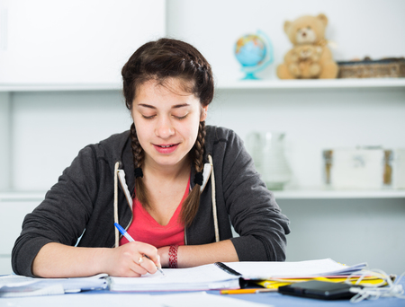 essays: Smiling female teenager reading educational materials at home