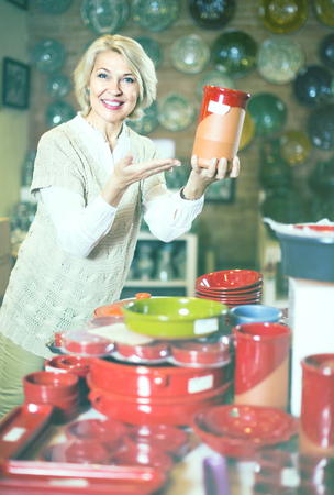 Mature woman buying ceramic vase in the shop