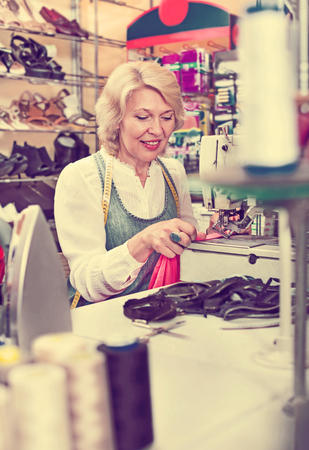 needlewoman: Portrait of professional female tailor working on sewing machine in the studio Stock Photo