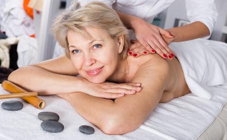 Senior female client enjoying relaxing massage in beauty salon