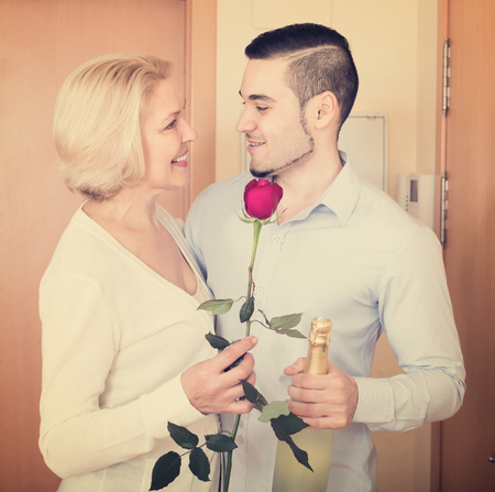 Smiling elderly woman meeting young handsome boyfriend with flowers and wine in hands at doorway