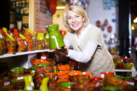 Senior happy blonde woman chooses ceramic ware in the cookware section at hypermarket
