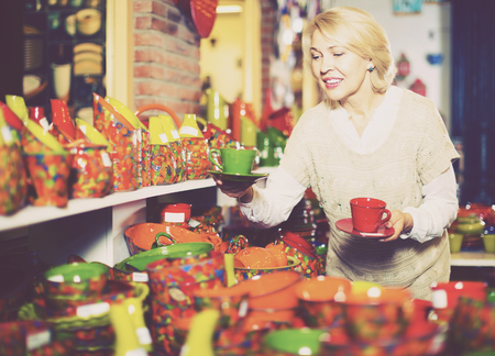 Portrait of mature woman buying ceramic tableware in shop cookware