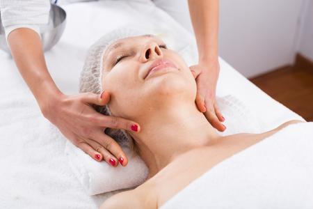 cliente mujer mayor que goza la cara de masaje relajante en salón de belleza Foto de archivo