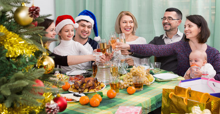 granny and grandad: Mature parents with positive adult kids and grandchildren celebrating Merry Christmas Stock Photo