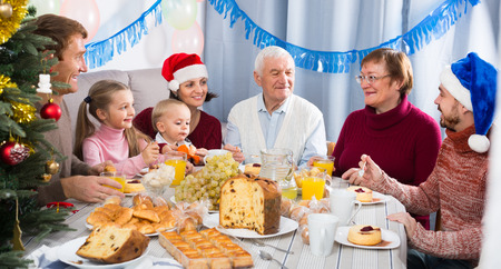 Positive family members making conversation during Christmas dinner Stock Photo