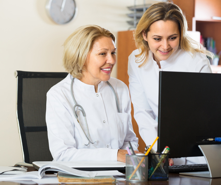 physiotherapists: Two positive female doctors in white overalls working with computer together