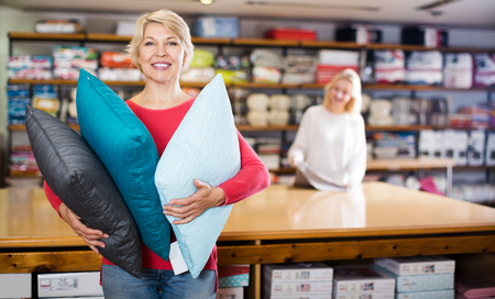 Smiling customer looking for bright pillow in home textile shop