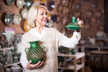 ware: Mature woman choosing and buying ceramic ware in the shop