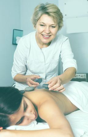 Smiling woman client having massage procedure in beauty salon Stock Photo