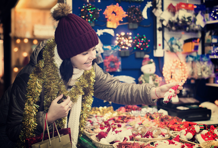 overspending: Nice teen  girl near the customer counter with Christmas decoration