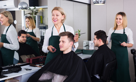 16s: Happy senior woman hairdresser serving teenager in chair Stock Photo