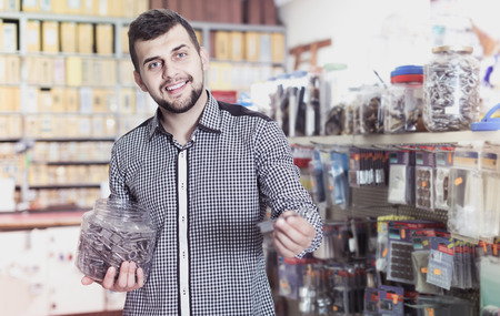 Young american man deciding on best DIY details in houseware store