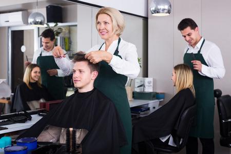 16s: Smiling senior female hairdresser serving teenager in chair
