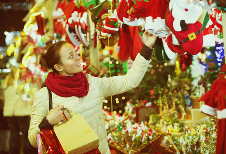 festal: Portrait of beautiful female customer near counter with Christmas gifts in evening time