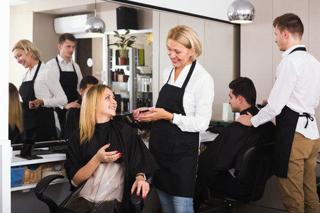 16s: Cheerful aged woman cutting girl hair in hairdressing saloon