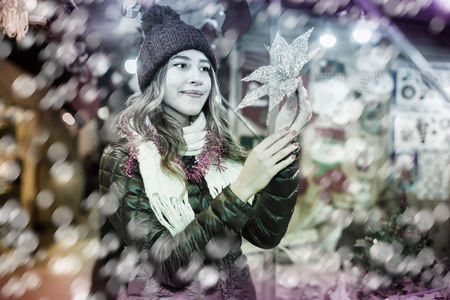 Portrait of young  happy  woman at Christmas fair  in evening