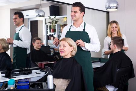 peignoir: Adult male stylist cutting hair of elderly blonde in salon. Focus on the woman