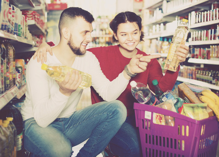 sunflower seeds: Happy family buying vegetable oil at grocery shop Stock Photo