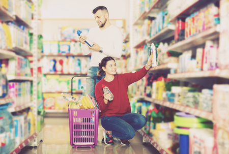 Glad couple buying detergents for house in the shopping mall Stock Photo