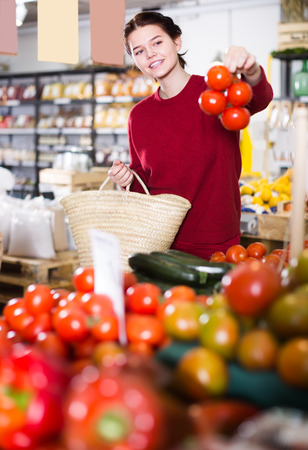 Portrait of positive young female customer selecting tomatoes in grocery store