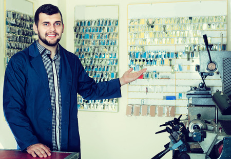neatness: Smiling american  male worker showing his tools for making keys in workshop Stock Photo
