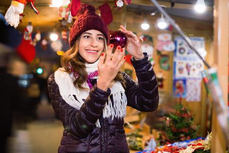 overspending: Happy girl choosing Christmas decoration at market