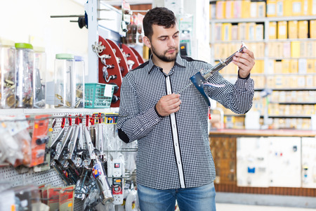 Man choosing new glue gun in houseware store Imagens - 77715581