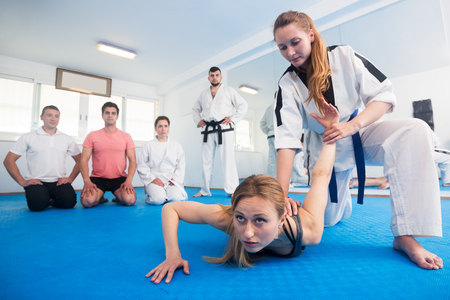 Young female trainer demonstrating painful hold to adults in taekwondo class Stock Photo