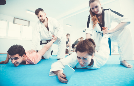 Female is taking selfies while training in pairs at taekwondo class.