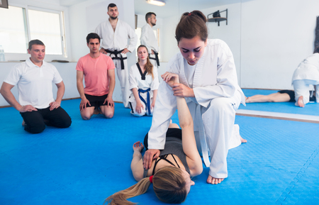 Young girls are training in pair to use taekwondo technique during class.