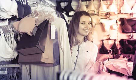 Young woman is enjoying her purchases in underwear shop. Stock Photo