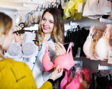 Smiling young woman seller assisting woman in choosing bra in underwear store Stock Photo