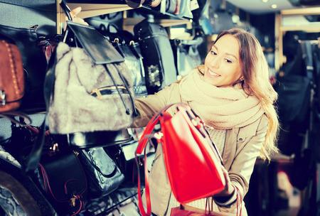 Ordinary girl choosing bag among assortment in store