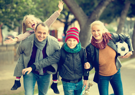 5s: Cheerful active family with two smiling children spending weekend together outdoors Stock Photo