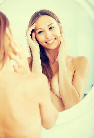 femme se deshabille: young naked smiling woman attentively looking at herself in mirror Banque d'images
