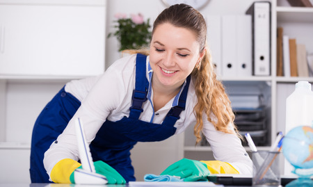 positiv: Young and smiling woman cleaning room from dust and dirt