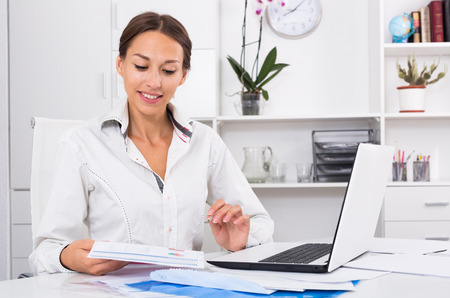 professional woman sitting with laptop and holding paper document in hands at company office