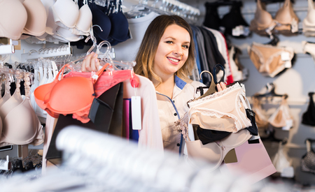 Smiling female is enjoying her purchases in underwear shop.