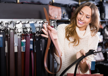 Smiling woman buying leather belts at clothing shop