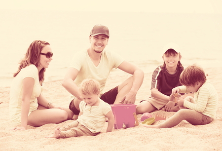 Happy family with three kids resting on sandy beach